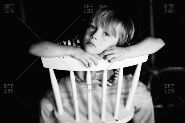 Portrait of boy leaning on a chair