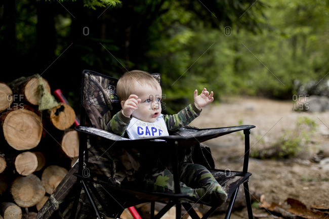 Baby boy in camouflage sitting in camp chair next to wood pile