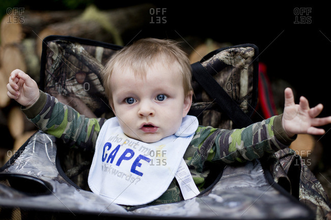 Baby boy sitting in a camouflage camp chair