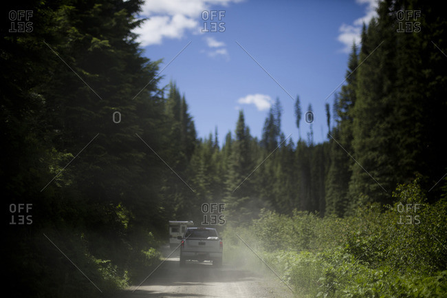 Camper and truck driving down dirt road in forest