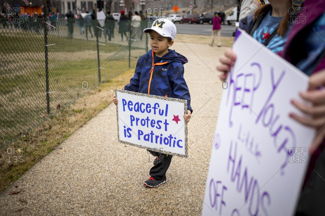 """Washington, D.C., USA - January 21st, 2017: The Women's March from the US Capitol building down the Mall to the Whitehouse. Young boy holding a sign that says """"Peaceful protest is patriotic"""""""