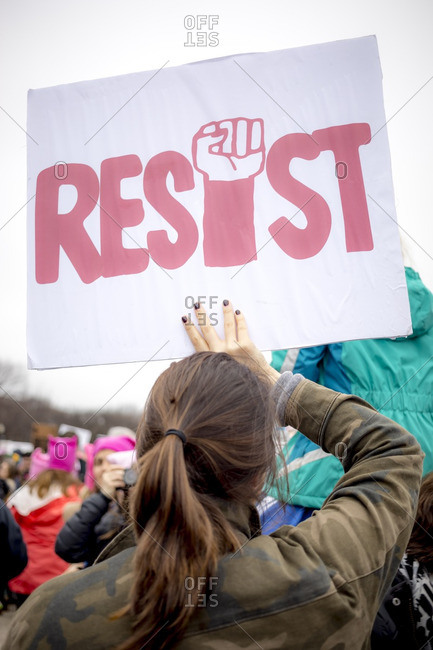 "Washington, D.C., USA - January 21st, 2017: The Women's March from the US Capitol building down the Mall to the Whitehouse. A woman holding a sign above her head that says ""Resist"""