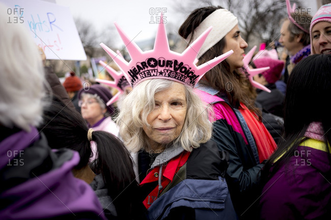 "Washington, D.C., USA - January 21st, 2017: The Women's March from the US Capitol building down the Mall to the Whitehouse. Older woman wearing a pink crown that says ""Hear our voice"""