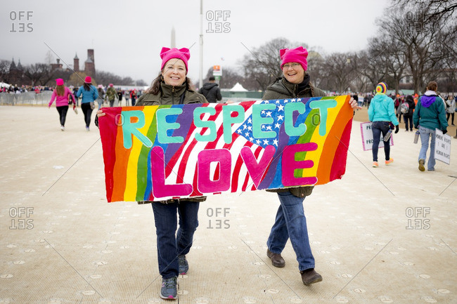 """Washington, D.C., USA - January 21st, 2017: The Women's March from the US Capitol building down the Mall to the Whitehouse. Two women in pink hats walking with a sign that says """"Respect love"""""""