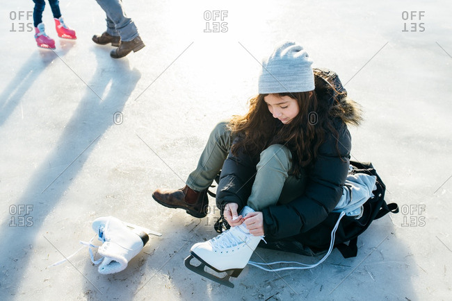 Young girl lacing up her ice skates