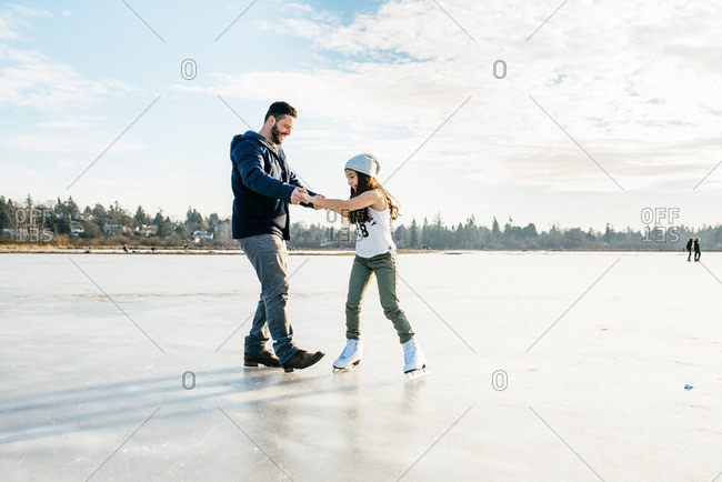 Father holding his daughter as she ice skates