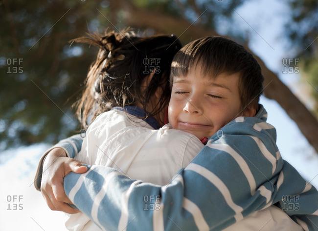 Boy hugging woman, smiling