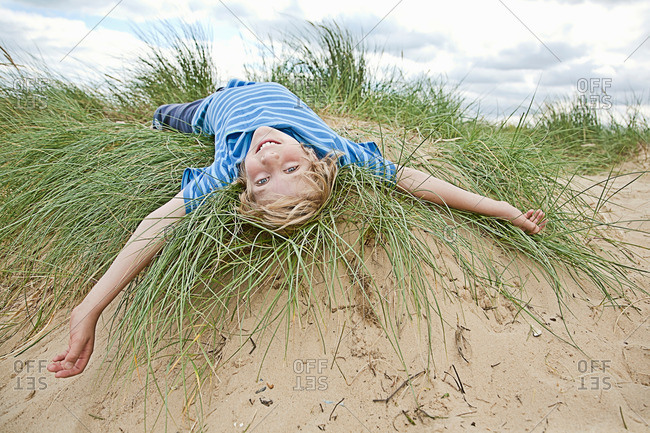 Boy playing in grass on beach