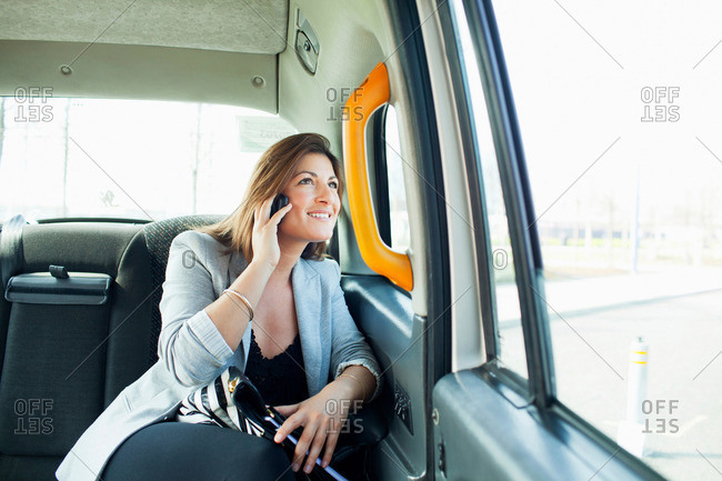 Businesswoman on cell phone in taxi