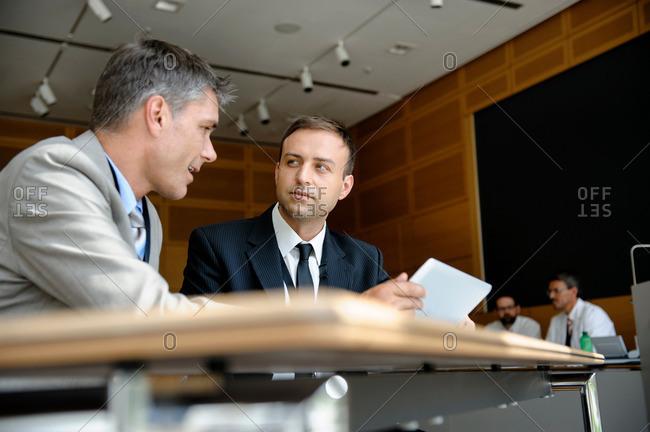 Businessmen using tablet computer at desk