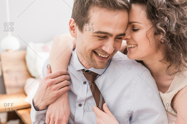 Mid adult couple face to face with arm around, smiling