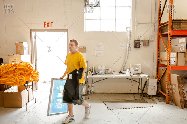 Worker carrying frame and t-shirt in screen printing workshop