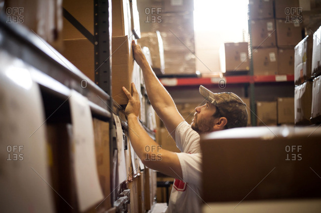 Worker reaching up for cardboard box stored in warehouse