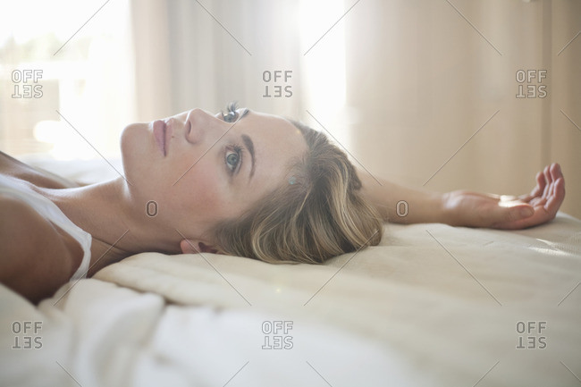 Close up of young woman daydreaming on bed