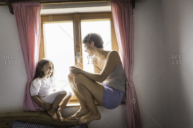 Young woman and daughter in holiday chalet, Tyrol, Austria