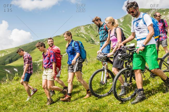 Group of friends mountain biking and hiking, Tyrol, Austria