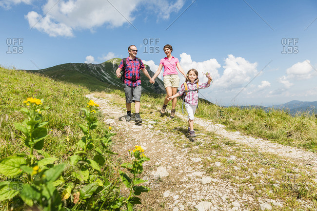 Parents and daughter walking on dirt track, Tyrol, Austria