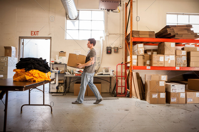 Worker walking through warehouse, carrying cardboard box