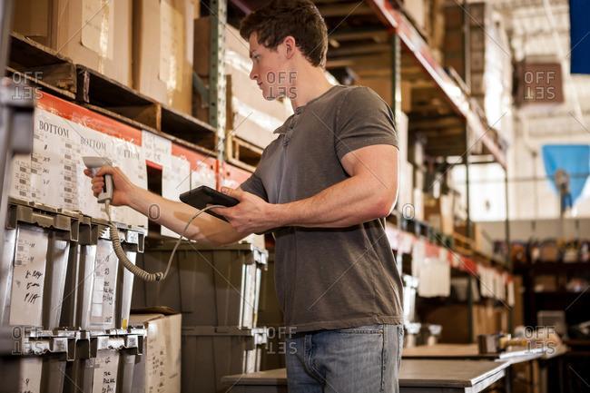 Worker in warehouse scanning barcode on cardboard box