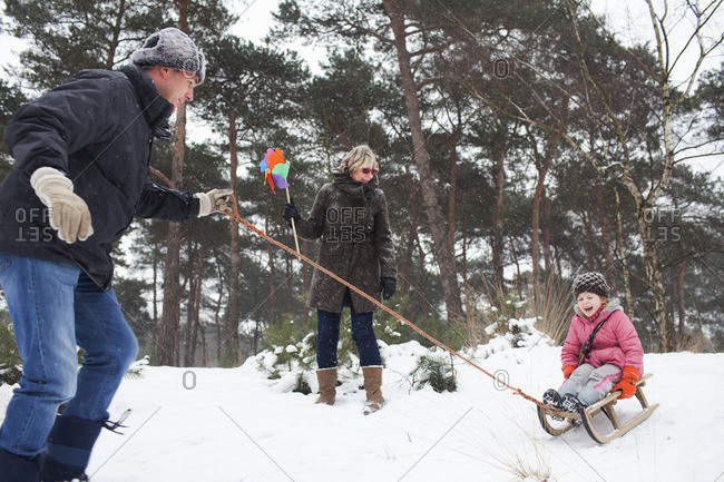 Father and grandmother pulling girl on toboggan in snow