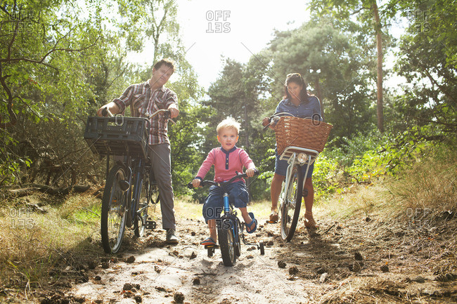 Family cycling though forest