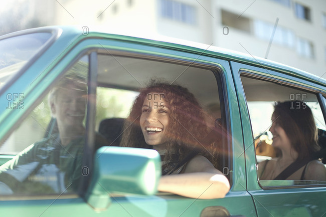 Young friends enjoying road trip in car