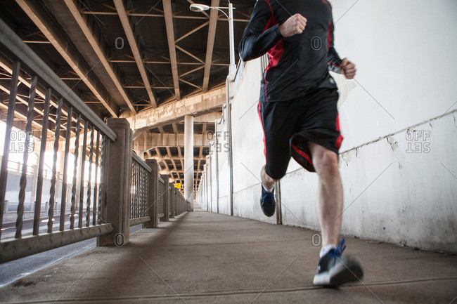 Cropped shot of young man running on city bridge