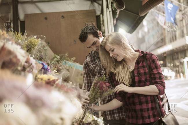 Young couple choosing flowers at flower stall
