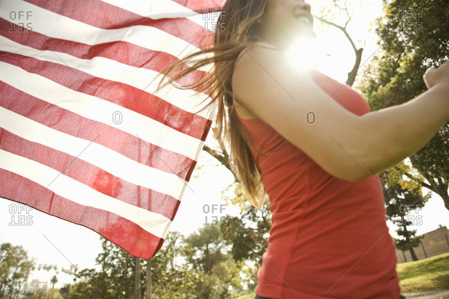 Close up of young woman running with American flag in park