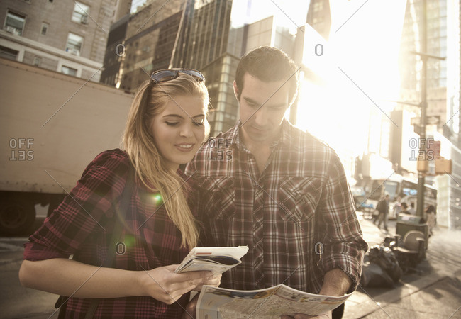 Young couple looking at maps, New York City, USA
