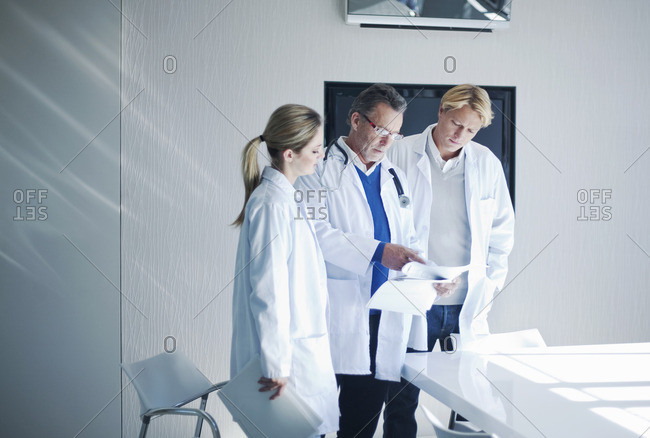 Senior doctor and trainees looking at medical records
