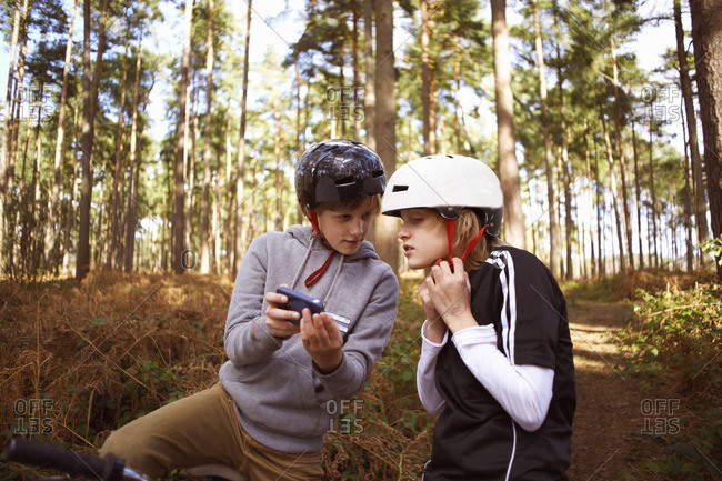 Twin brothers on bikes in forest looking at smartphone