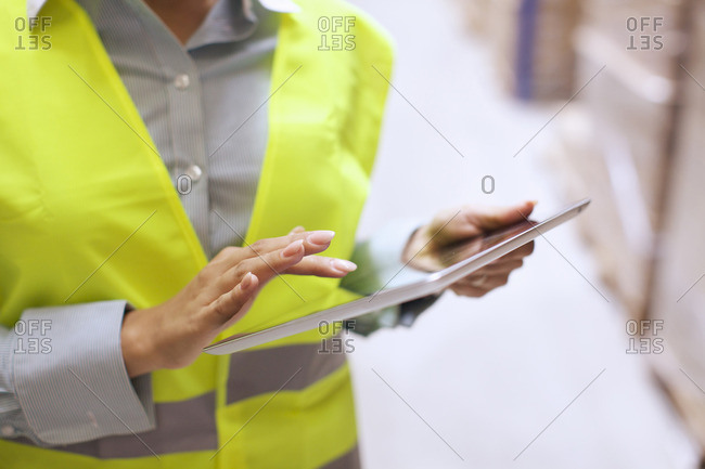 Cropped shot of female warehouse worker using digital tablet