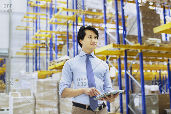 Male manager using digital tablet in distribution warehouse