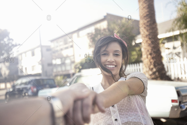 Young woman holding boyfriends hand on suburban street