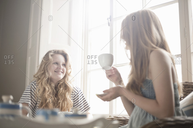 Two teenage sisters sharing traditional afternoon tea
