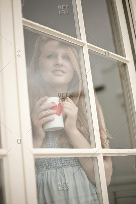 Teenage girl holding a coffee mug looking out of window