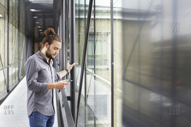 Man using smartphone in corridor