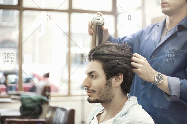 Barber spraying hairspray on customer's hair