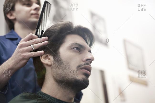 Hairdresser combing customer's hair