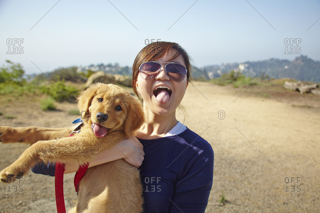 Young woman holding Labrador puppy, tongues out