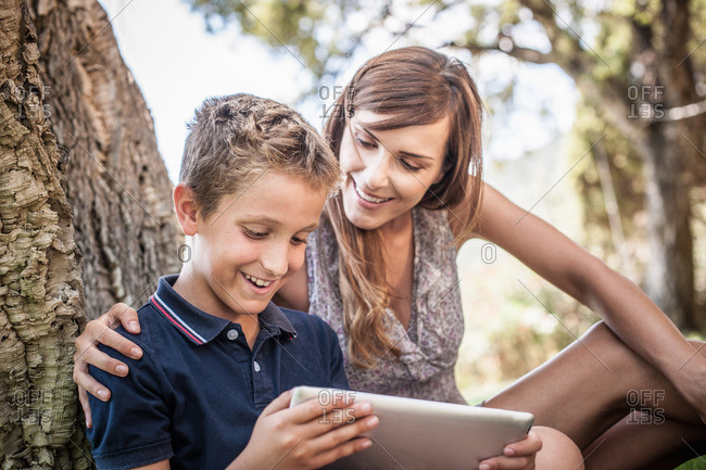 Mother and son looking at digital tablet in holiday home garden, Capoterra, Sardinia, Italy