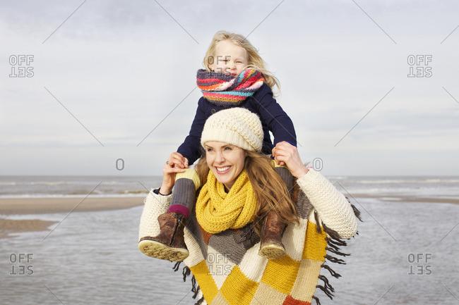 Mid adult woman shoulder carrying daughter on beach, Bloemendaal aan Zee, Netherlands