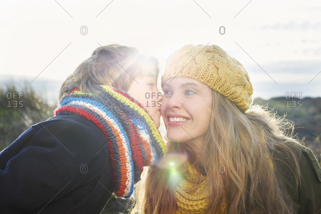 Mid adult woman with son kissing her cheek at coast