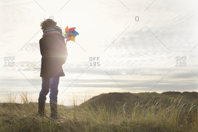 Rear view of boy holding up paper windmill at coast