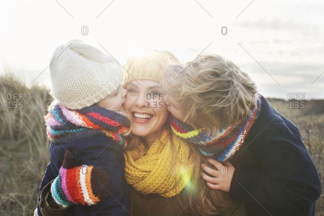 Mid adult woman with son and daughter kissing her cheek at coast
