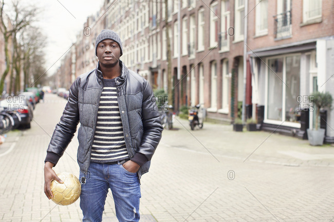 Portrait of young man on street holding soccer ball, Amsterdam, Netherlands