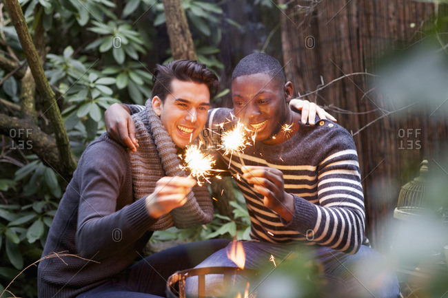Two young men crouching in front of garden fire with sparklers