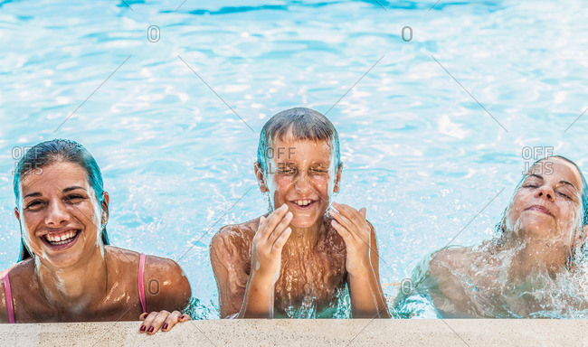 Portrait of boy and two sisters in swimming pool