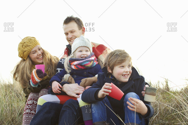 Smiling mid adult couple with two children at coast